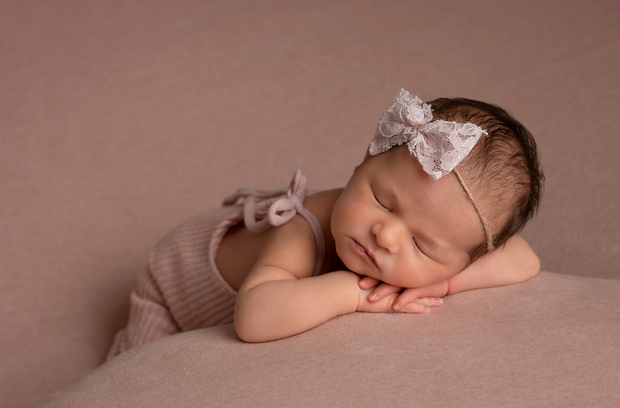 newborn photographer west sussex brightography baby girl asleep on pink blanket with romper and bow headband