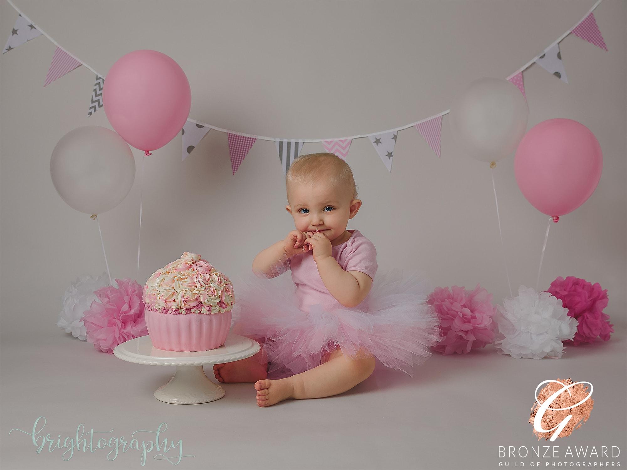 baby girl with pink giant cupcake and tutu at brighton cake smash photoshoot