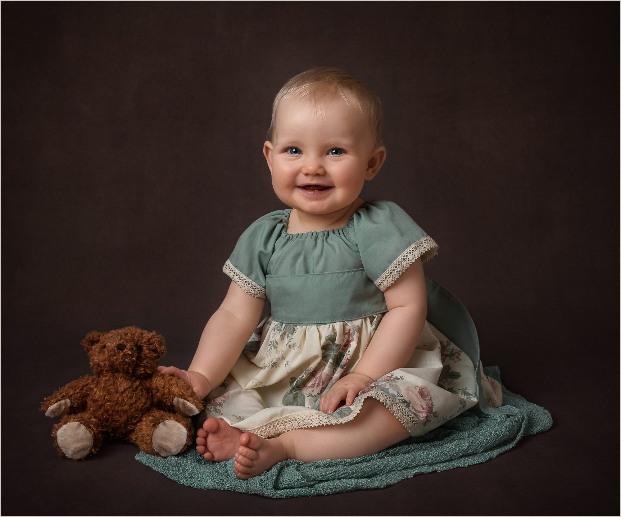 9 month old girl sitting in brighton studio for baby photoshoot with brown backdrop and teddy and green dress