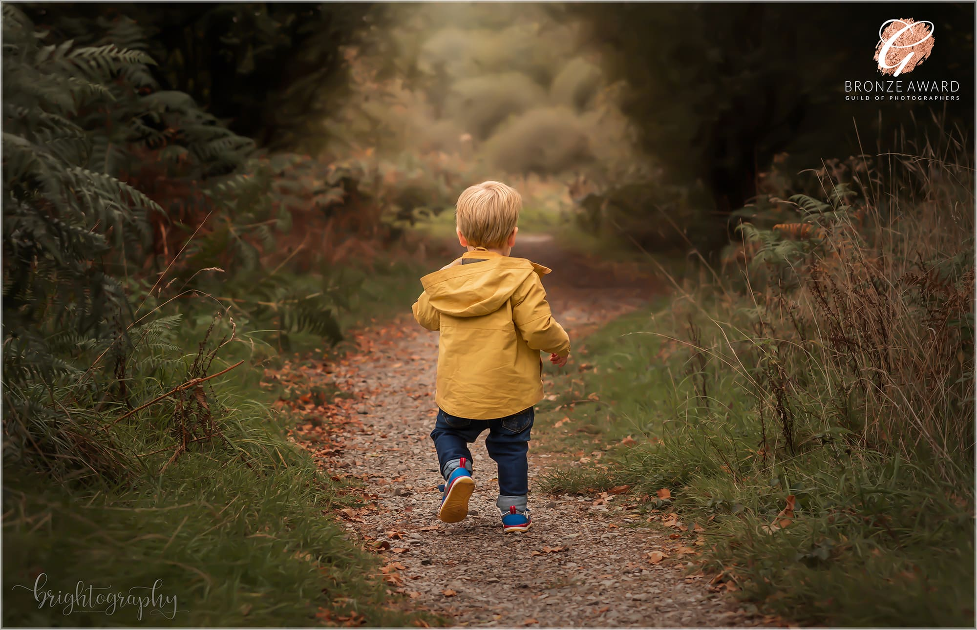 toddler dressed in mustard jacket running through autumnal ferns and trees