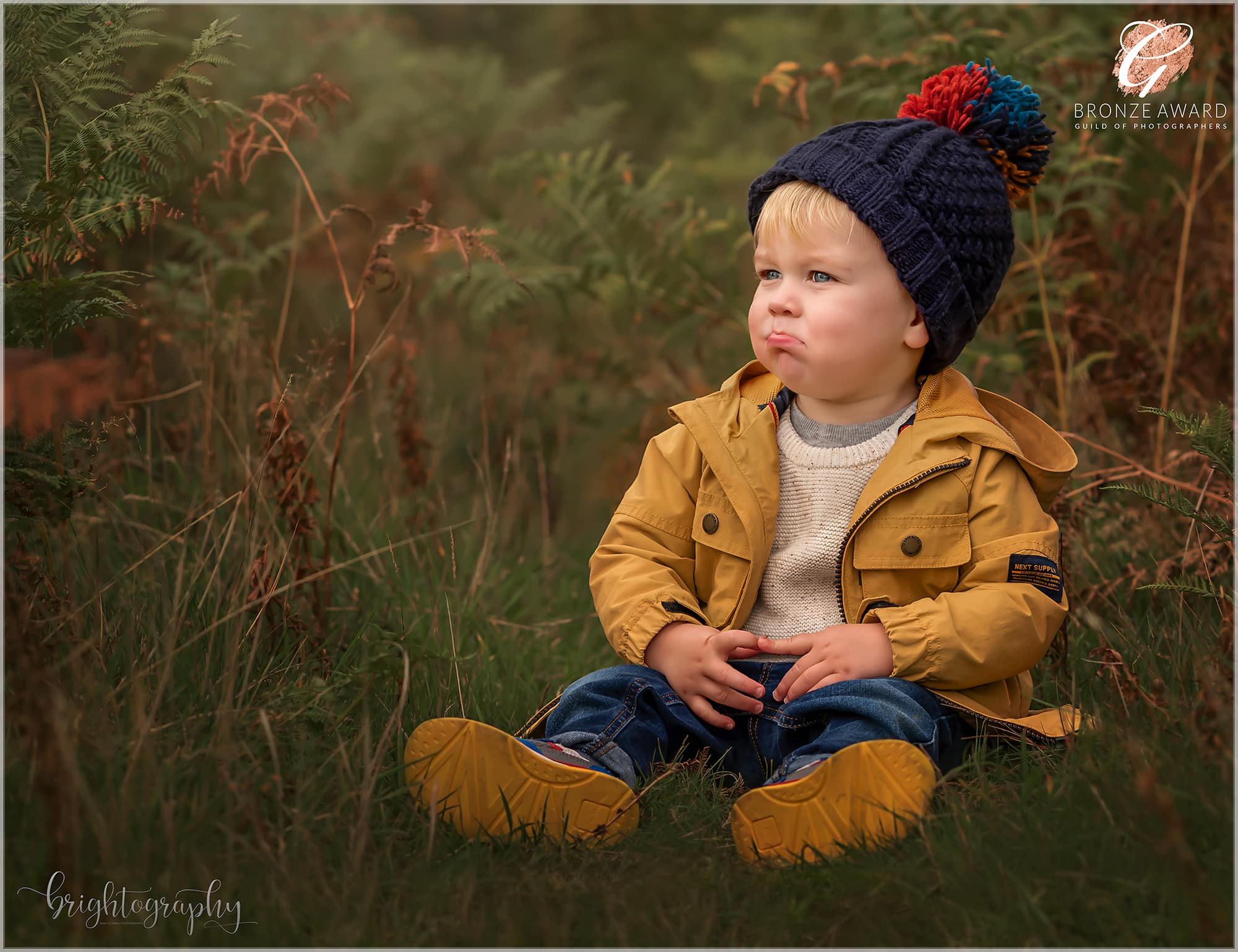 toddler dressed in mustard jacket and navy bobble hat sat in autumnal ferns